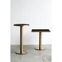 Mesa de bar con sobre de cristal negro y pie dorado