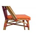 Silla de terraza con estructura metálica Celine y ratán sintético rojo y naranja.
