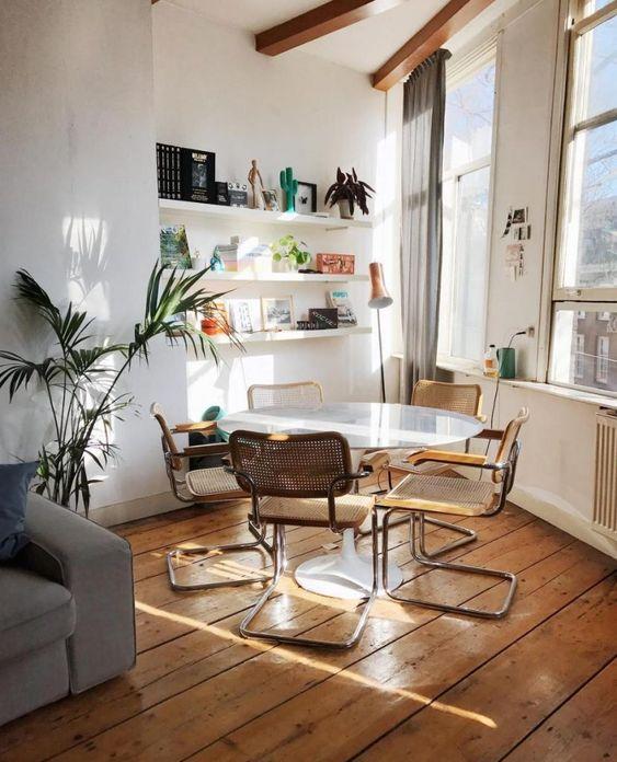 Comedor con mesa Tulip y sillas de diseño Cesca con brazos.