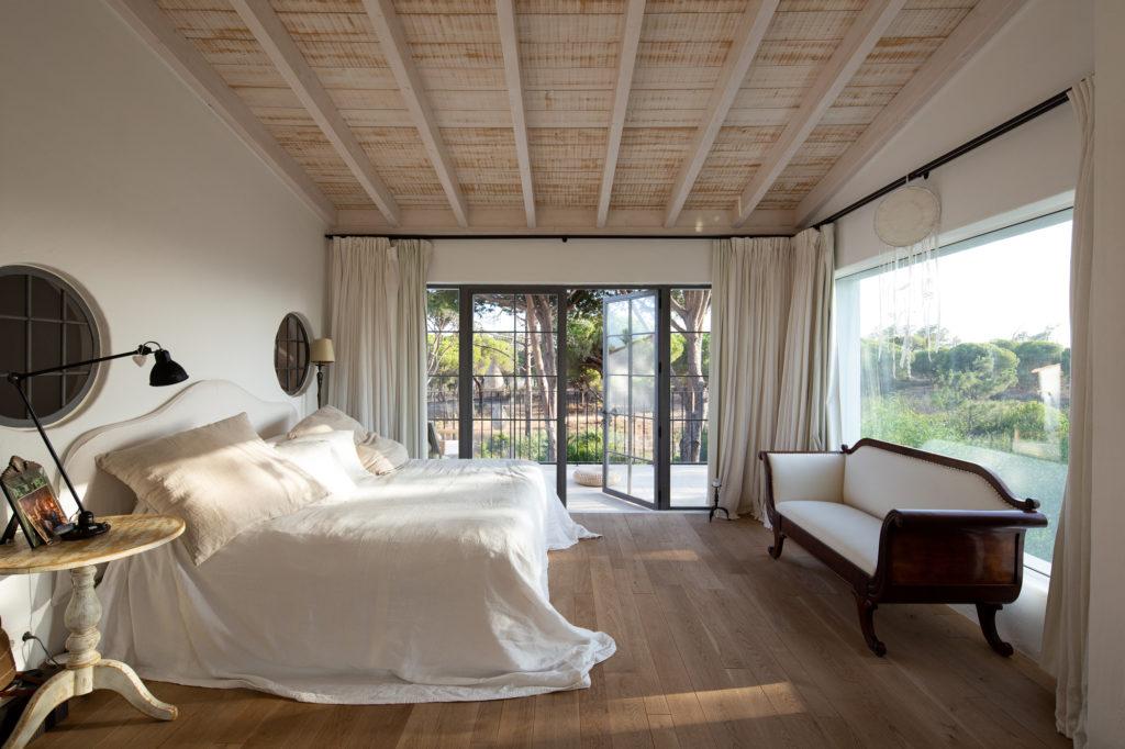 Dormitorio con cama y sofás estilo rústico
