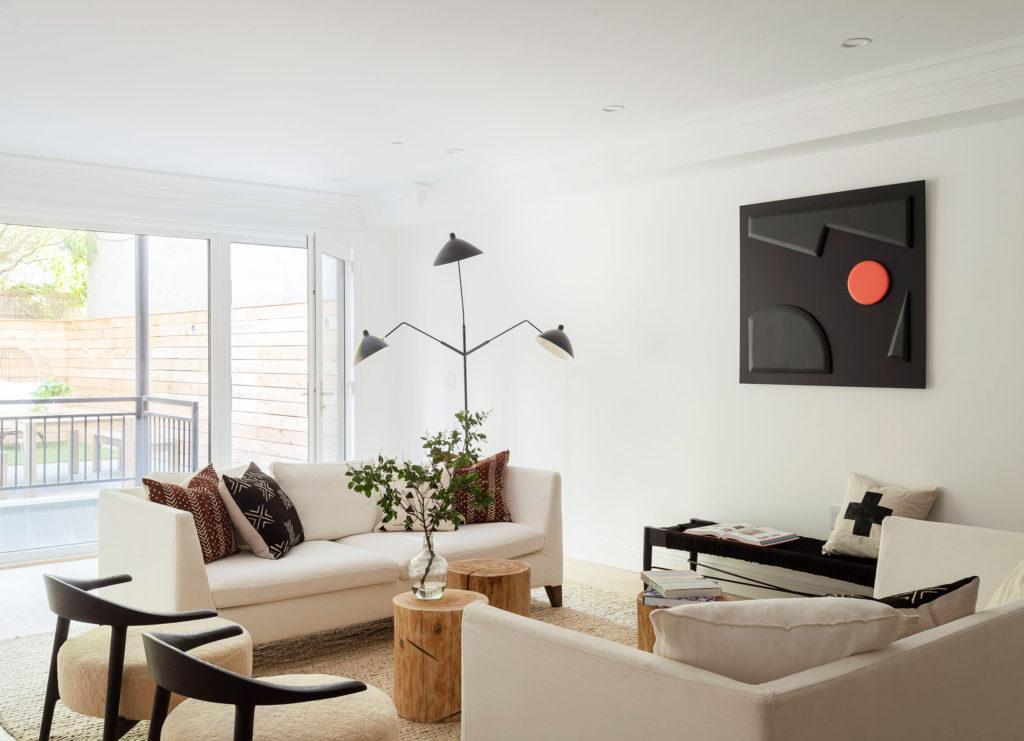 Salón minimalista en tonos claros con lámpara de pie.