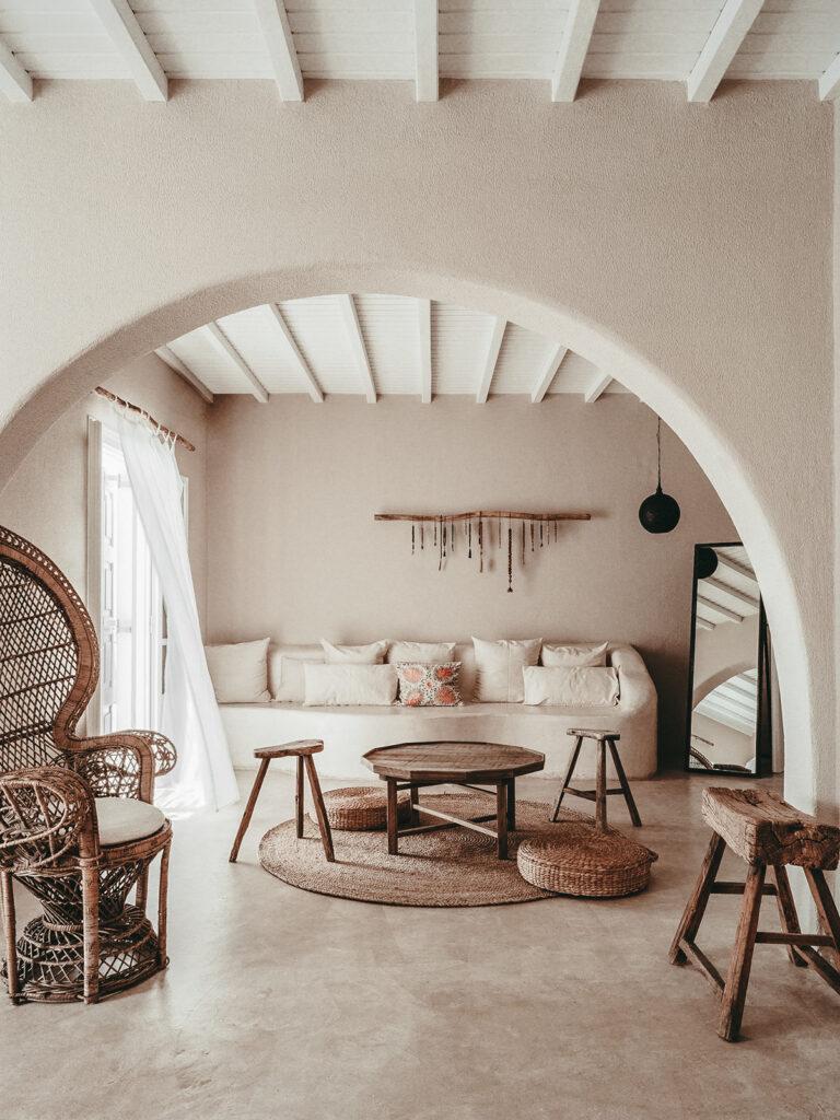 Salón decorado con alfombra y puf de mimbre