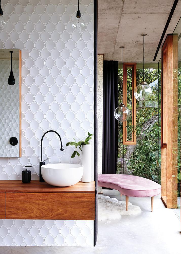 baño con grandes ventanales y banco rosa pastel