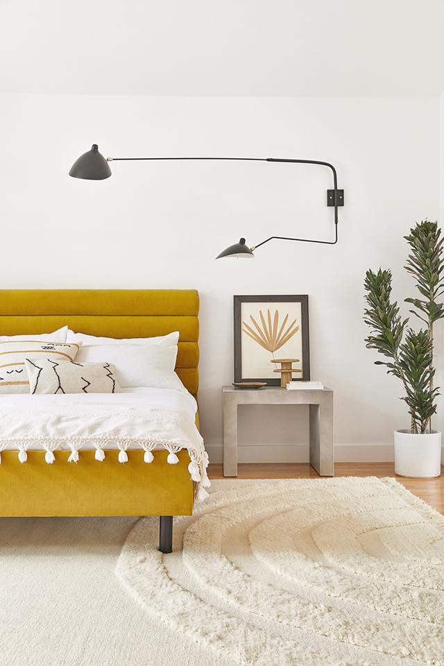 dormitorio con cama y cabecero en terciopelo mostaza