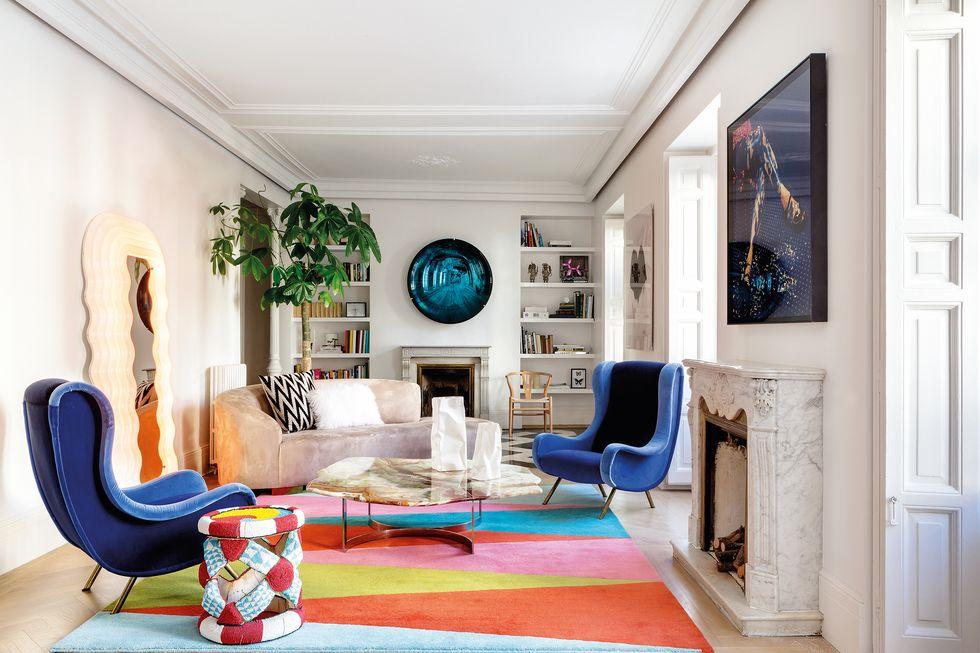 precioso salón estilo años 70 con chimenea y sillones de terciopelo azul